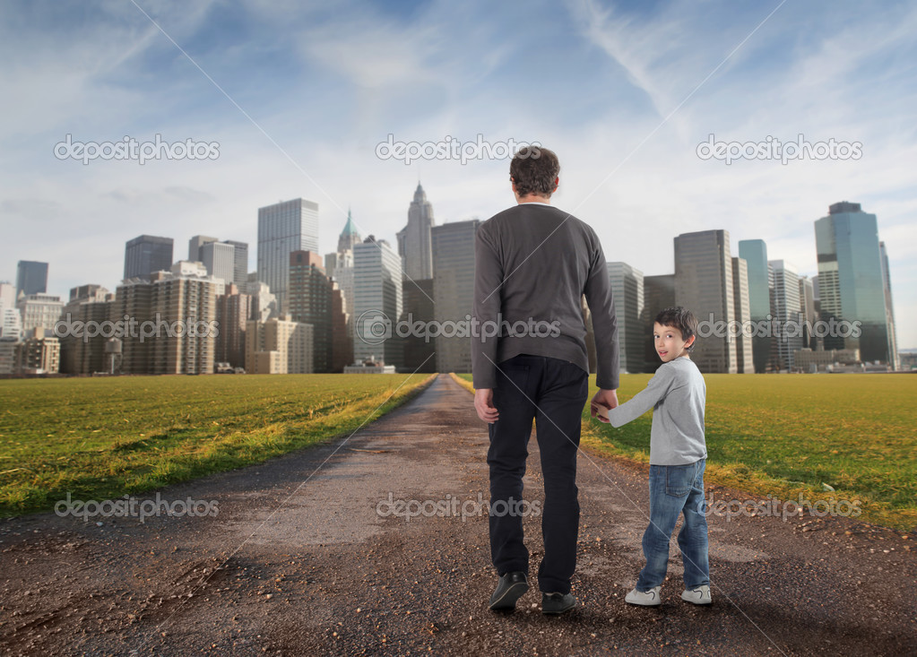 Portrait of a man hand in hand with a child walking towards a city — Stock Photo #2489564