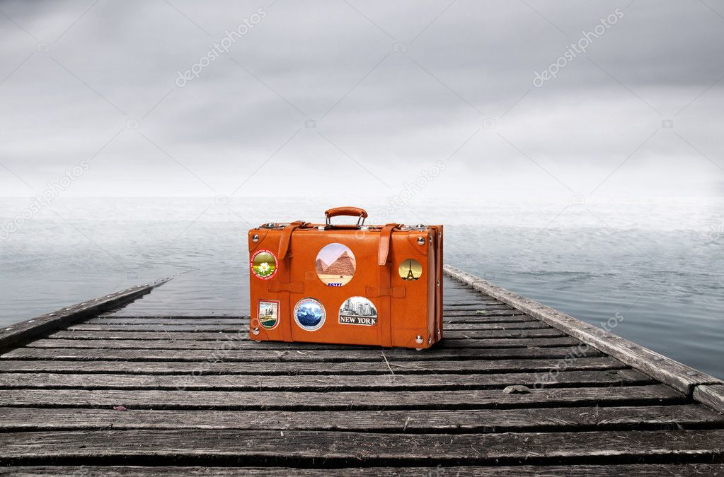 Suitcase lying on a dock in front of the sea — Stock Photo #2489566