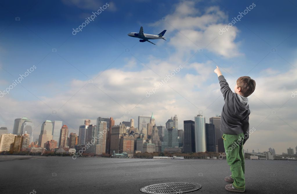 Portrait of a child pointing at an airplane flying over a city — Stockfoto #2489592