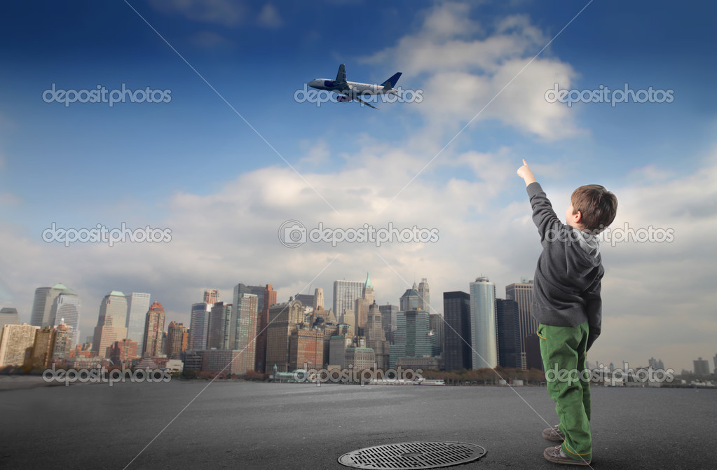Portrait of a child pointing at an airplane flying over a city — Stock Photo #2489592