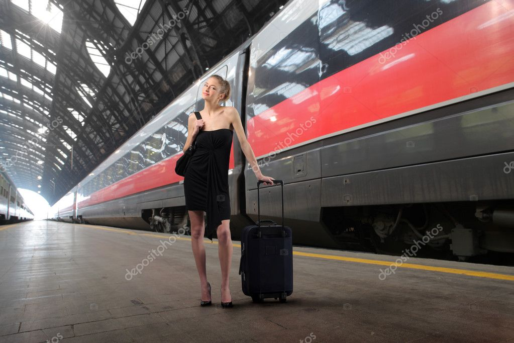 Young elegant woman with suitcase standing on the platform of a train station — Lizenzfreies Foto #2505345