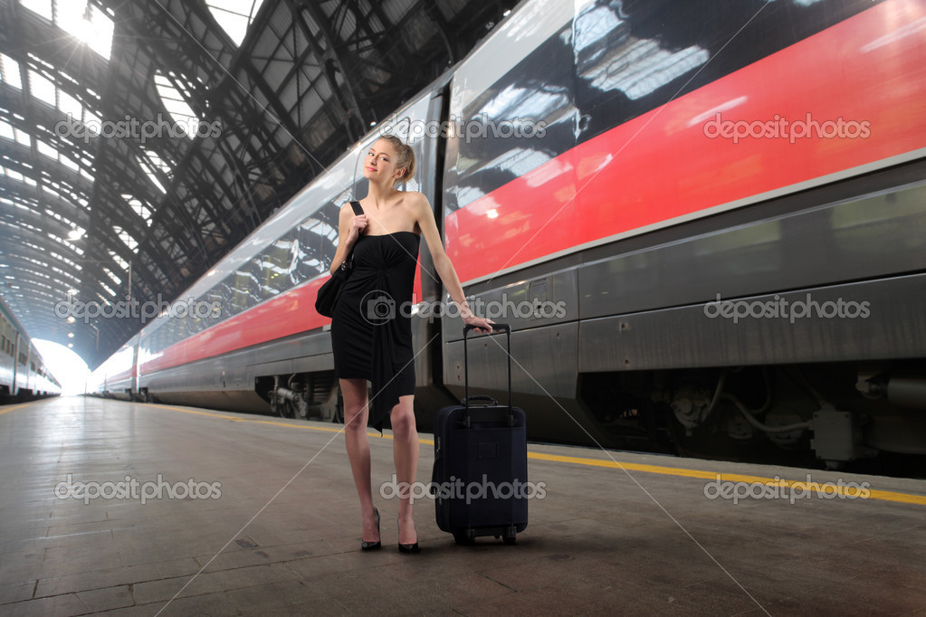 Young elegant woman with suitcase standing on the platform of a train station — Stock Photo #2505345
