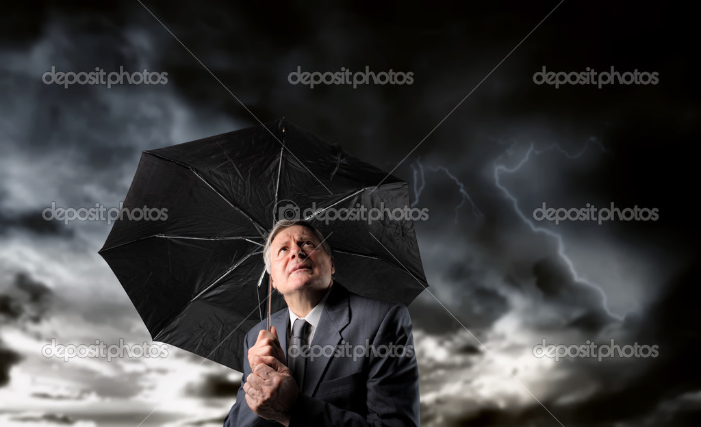 Senior businessman standing under an umbrella with stormy sky above him — Stock Photo #2519521
