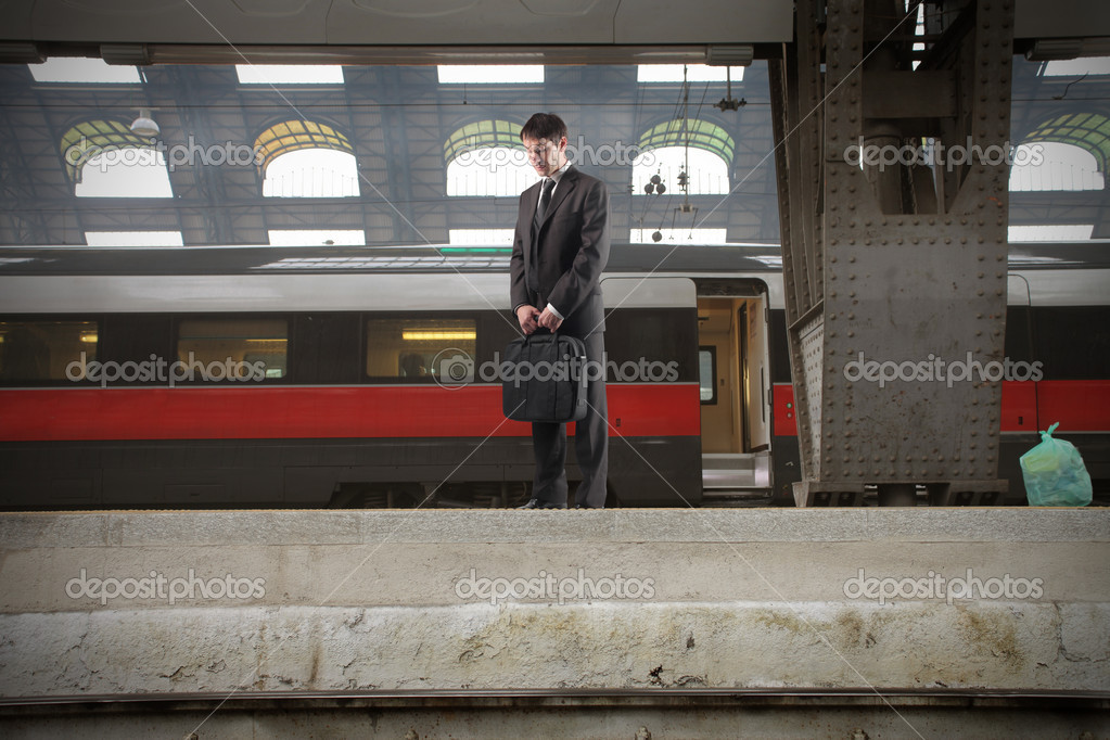 Businessman standing on the platform of a train station  Stock Photo #2539255