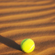 Stock Photo: Tennis ball in desert sand