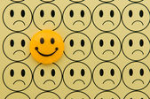 Yellow smiley against sad emoticon — Stock Photo