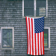 Постер, плакат: U S Flag hanging on building