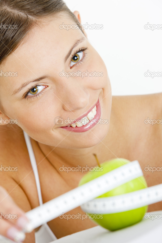 Portrait of young woman with green apple and tape measure — Stock Photo #2434920