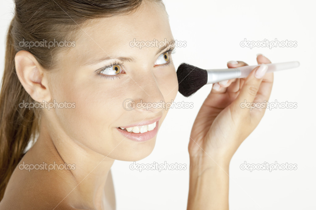 Portrait of young woman putting on face powder — Foto Stock #2552629