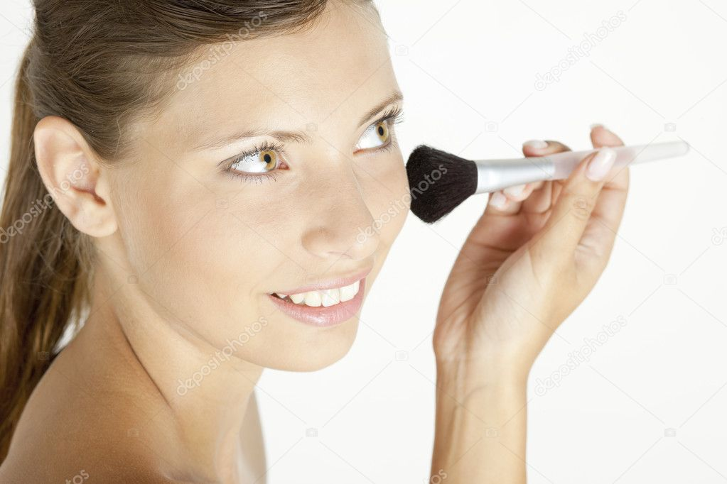 Portrait of young woman putting on face powder — Stok fotoğraf #2552629