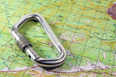 Carabiner on map background — Stock Photo