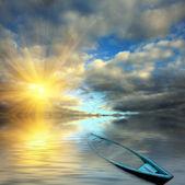 Flooded boat on sunset background — Stock Photo