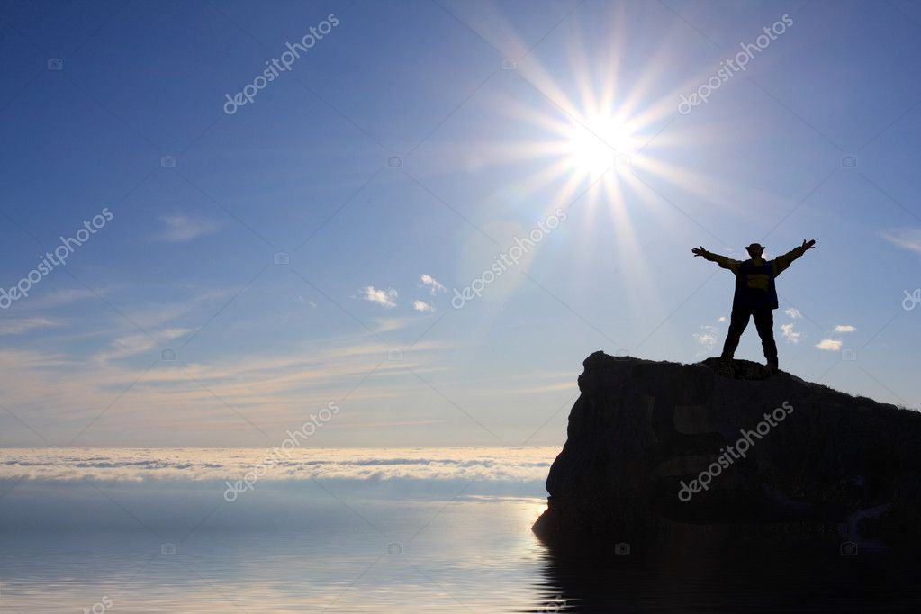 Man silhouette on the rock over sea on sunshine background — Stock Photo #2621689