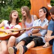 Four young friends play the guitar — Stockfoto