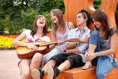 Four young friends play the guitar — Stock Photo