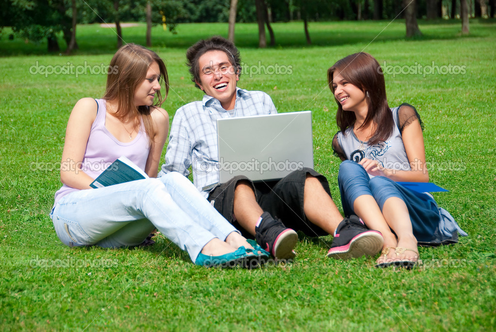 Three students relax and talking on the grass in the park  Stock Photo #2470562