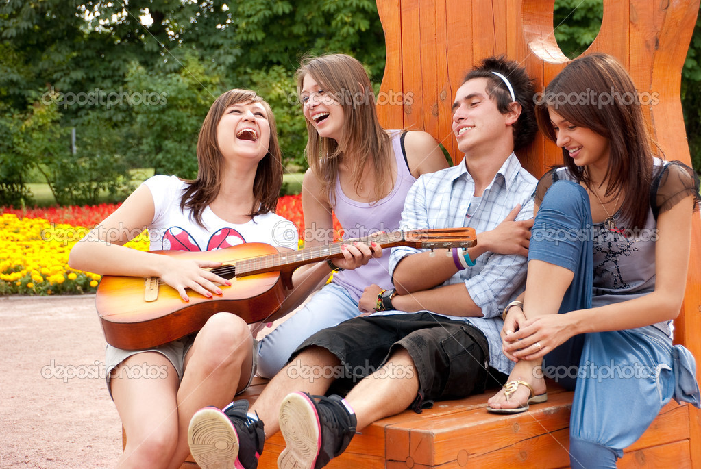Four young  friends play the guitar and laughing outdoors  Stock Photo #2470579