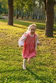 Small girl fun runs in a park — Stock Photo