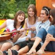 Stock Photo: Four young friends play guitar