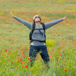 Happy hiker on a poppy field — Stock Photo #2606950