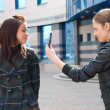 Two girls take pictures on a street — Stock Photo #2609005