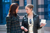 Two girls on a street with coffee — Stock Photo