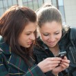 Young girls watch something in mobile - Stock Photo
