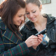 Young girls watch something in mobile — Stockfoto