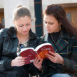 Two girls students read textbook - Stock Photo