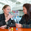 Two girls drink water in food court — Foto de Stock