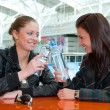 Two girls drink water in food court — Stock Photo