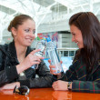 Two girls drink water in food court — Stockfoto