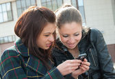 Young girls watch something in mobile — Stock Photo