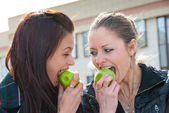 Happy girls eat green apples outdoors — Stock Photo