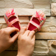 Stock Photo: Small pink baby shoes on stone wall