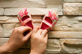Small pink baby shoes on stone wall — Stock Photo