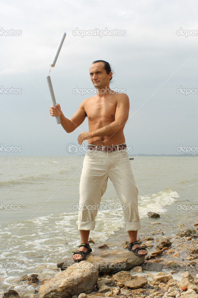 The man trains with nun-chakami on the bank of a gulf — Stock Photo #2537160