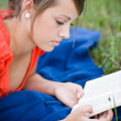 Foto Stock: Young girl relaxing and reading a book