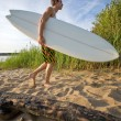 Stock Photo: Man walking at the beach with surfboard
