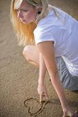 Blonde frau, die ein herz zeichnen — Stockfoto