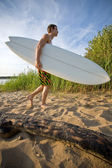 Man walking at the beach with surfboard — Stock Photo