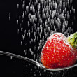 Icing sugar falling on a strawberry — Stock Photo