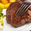 Closeup of a silver fork on a steak - ストック写真