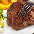 Closeup of a silver fork on a steak - Stockfoto