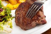 Close-up van een zilveren vork op een biefstuk — Stockfoto