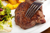 Closeup of a silver fork on a steak — Stockfoto