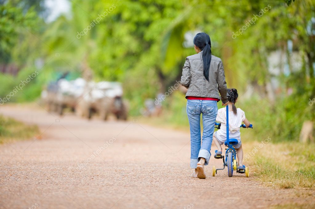 Mother guiding her daughter on a bike — Stock Photo #2495705