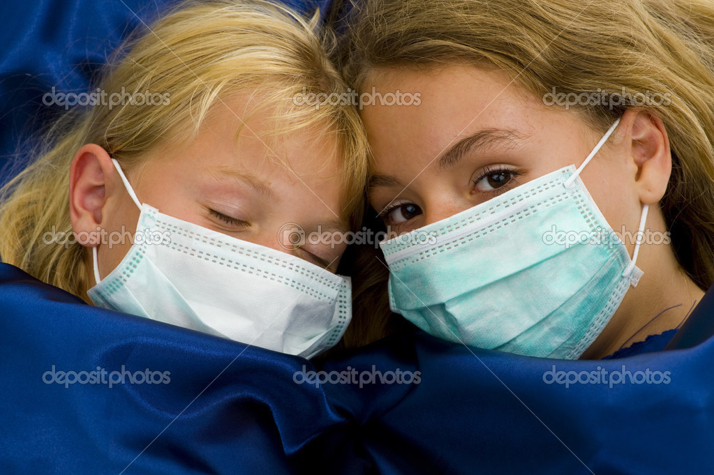 Two girls with protective masks sick in bed — Stock Photo #2499745