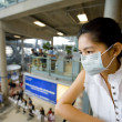 With flu mask at the airport — Stock Photo
