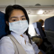 Woman with protective mask in a plane — Stock Photo #2542553